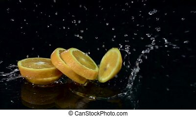 Orange dissolves into slices when it falls into the water. Black background. Slow motion