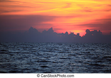 Orange drama sunset over dark gloomy sea