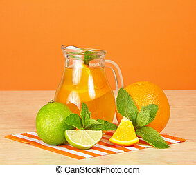 Orange drink, citrus, mint and striped napkin on a table