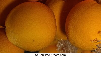 Orange Drops Under Water on Black Background. Fresh Orange Fruit Plunging And Splashes Water. Water Air Bubbles