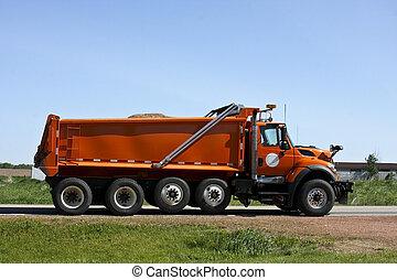 orange dump truck loaded going down a highway