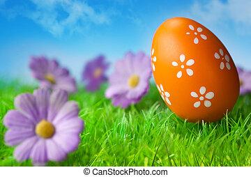 Orange easter egg in the grass against blue sky