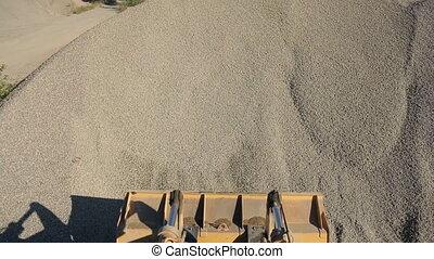 Orange excavator bucket scoops up crushed stone, view of top.