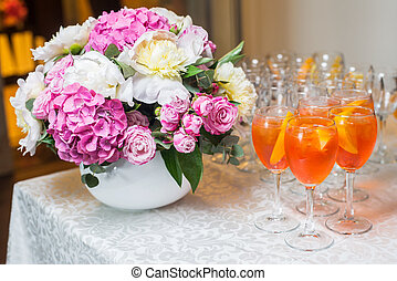 Orange exotic cocktail served at the table with a bouquet of flowers.