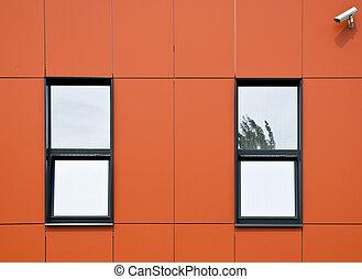 Orange facade of aluminum panels. Two windows and...