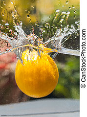 Orange falling into water close up