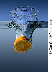 Orange falls into water on a blue background