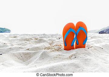 Orange flip-flop on the beach