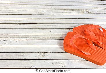 orange flip-flops on wood