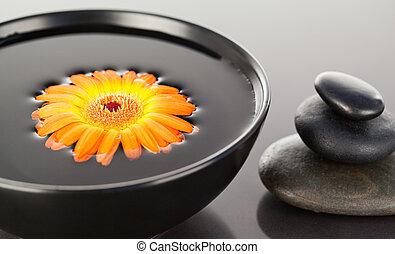 Orange flower floating on a black bowl and a stack of black pebbles