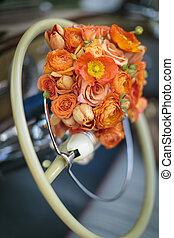 Orange flower wedding bouqet tied to a steering wheel of a vintage car