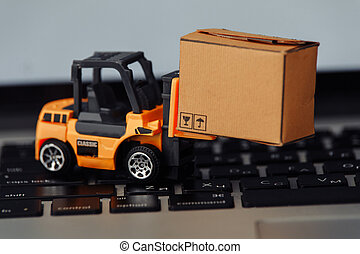 Orange forklift model and carton box on a keyboard close-up. Courier service concept