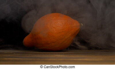 orange fresh pumpkin on a black background in smoke,...