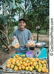 Portrait of happy farmer selling orange fruit