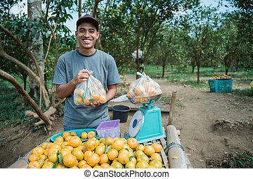 Portrait of happy farmer selling orange fruit with plastic bag