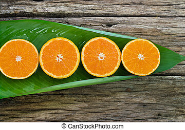 Orange fruit Slices on leaf and wooden background, nature concep