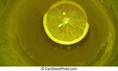 Orange fruit splashing slow motion in juice