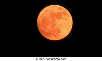 Orange full moon over dark sky