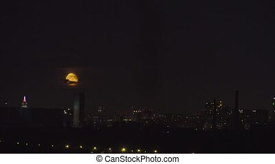 Orange full moon rising above Moscow skyline.
