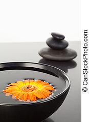 Orange gerbera floating on a black bowl and a stack of black pebbles
