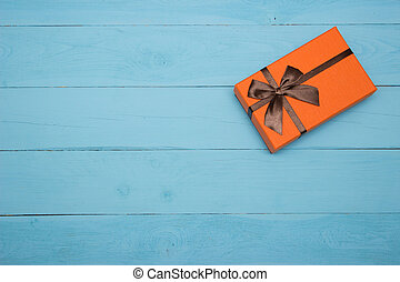 orange gift box on a blue wooden background