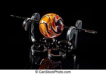 Orange glass bead on stand on black background