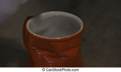 Orange glass pours hot cappuccino in the cafe