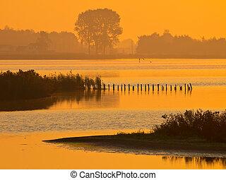 orange glow during sunrise over lake zuidlaardermeer