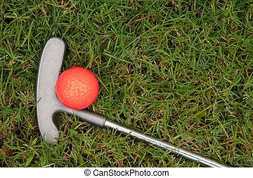 Orange golf ball and putter on green grass