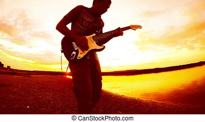 orange guitarist musician man playing a solo on electric guitar by the river at sunset sky clouds