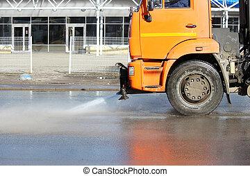 Orange harvesting machine washes car road in spring.