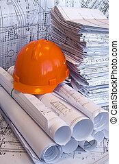 Orange helmet and heap of project drawings