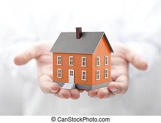 Orange house miniature in hands