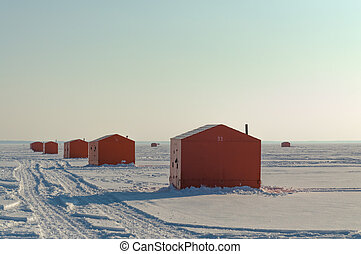 Ice fishing huts on a frozen lake in Ontario at sunset