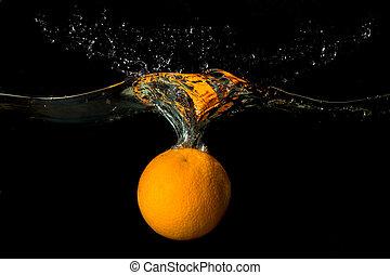 Orange in water on a dark background