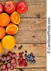 Orange juice, fresh oranges, apples, grapes, raspberries and blueberries on a wooden table - view from above - vertical photo - left orientation frame
