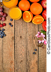 Orange juice, fresh oranges, apples, grapes, raspberries, blueberries and spring flowers on a wooden table - view from above - vertical photo