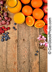 Orange juice, fresh oranges, apples, grapes, raspberries, blueberries and spring flowers on a wooden table - fruit background - view from above - vertical photo