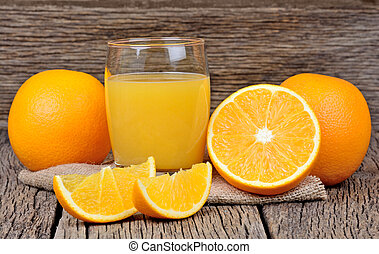 Orange juice in a glass and fruit on table