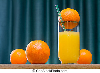 Orange juice in a glass and oranges on the table.