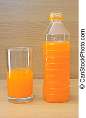 Orange juice in plastic bottle and glass on table
