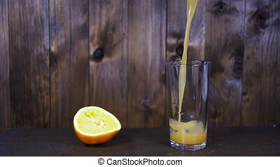 Orange Juice is Poured into a Glass on a Wooden Background. Slow Motion