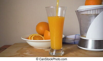 Orange juice is poured into a glass