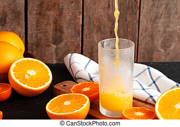 Orange juice pouring from the bottle into the glass