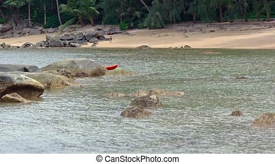Orange Kayak Slowly Emerges from Behind Rock near Tropical...
