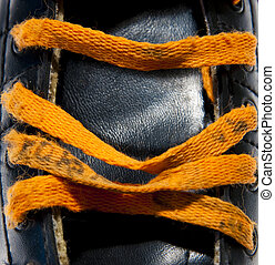 Orange laces on a black skate. Could be a roller skate, ice ...
