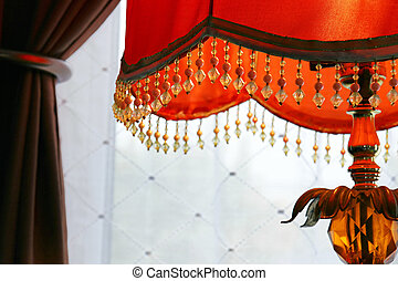 Orange lamp against drapes - Interior home decor detail: ...