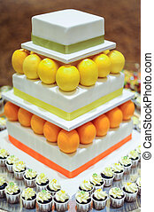 Orange Lemon 3 tier white wedding cake with mini cupcakes