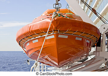 A large orange lifeboat hanging on the side of a ship