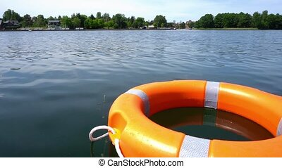 Orange life rescue buoy floating on lake water far from ...